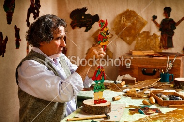 Master of the Turkish Shadow Puppet Tradition, Karagoz and Hacivat. Puppet Master is working on a new shadow puppet character in studio, Turkey