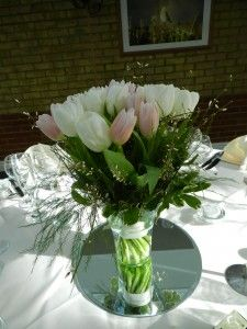 A guest table vase display of tulips on a mirror