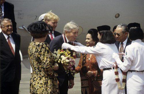 Staatsbezoeken. Aankomst Koninklijke familie op vliegveld Halim Perdana, Jakarta, Indonesië 21 augustus 1995. Prins Claus krijgt na aankomst een bloemenkrans omgehangen gadegeslagen door Koningin Beatrix, kroonprins Willem-Alexander en Hans van Mierlo.