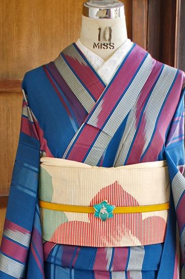 スモークがかった味わい深い青色の地に、斜めの絣模様もモダンな縞模様が織り出された、昭和レトロ・大正ロマンなムードただよう単着物です。