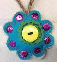 Blue felt flower w purple sparklies. Made by Dalma.