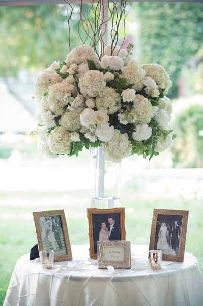 Wedding reception decor idea - photo display honoring late loved ones + elegant, tall white hydrangea, ivory rose + curly willow flower arrangement {Meredith Rogers Photography}