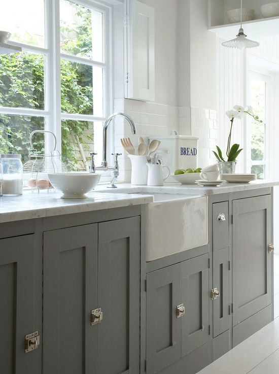 Grey painted cabinets with contrasting white marble worktops. We definitely advocate running window sills down to worktop level where possible to allow all available light to flood across the work-surface. Also note the prismatic glass pendant. Great look in the kitchen..