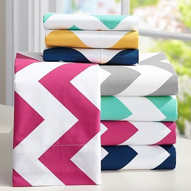 Magenta and turquoise chevron sheets with white comforter and multi quilt at the foot of the bed against gray walls.