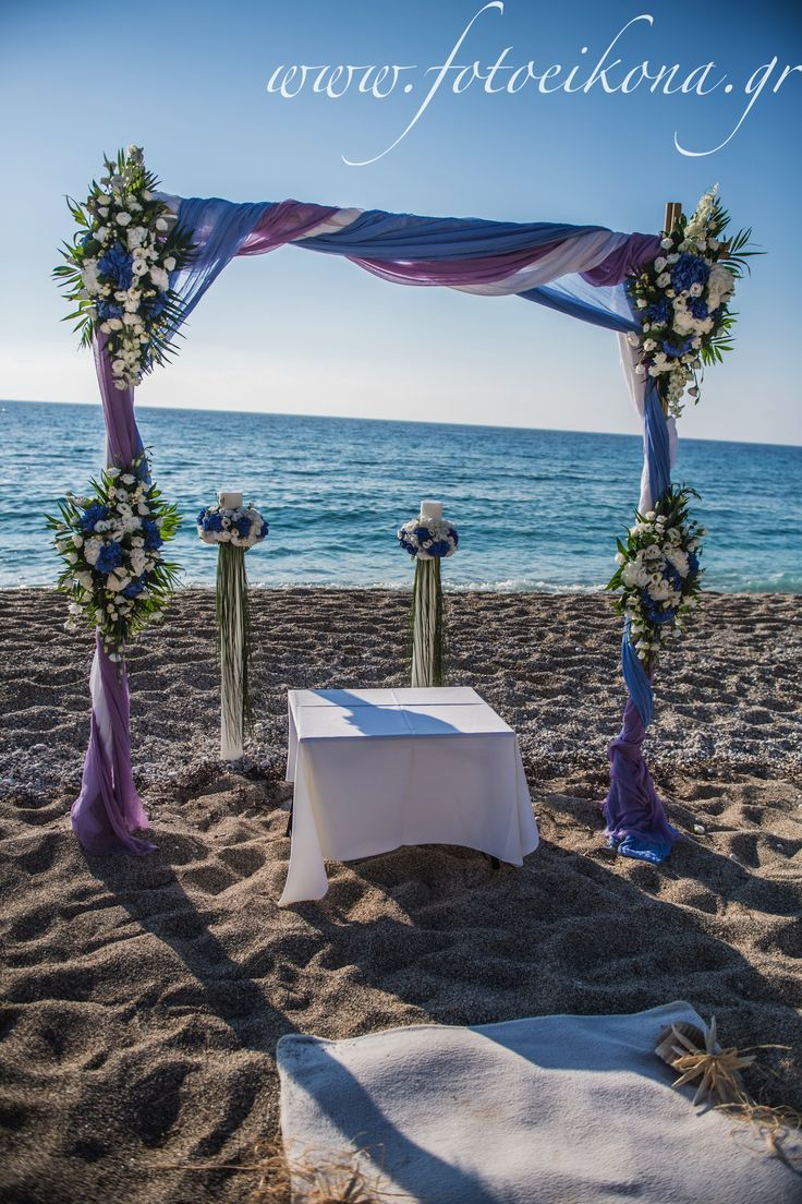 Orthodox beach wedding blessing in Lefkada with arch and lampathes candles. White and blue theme