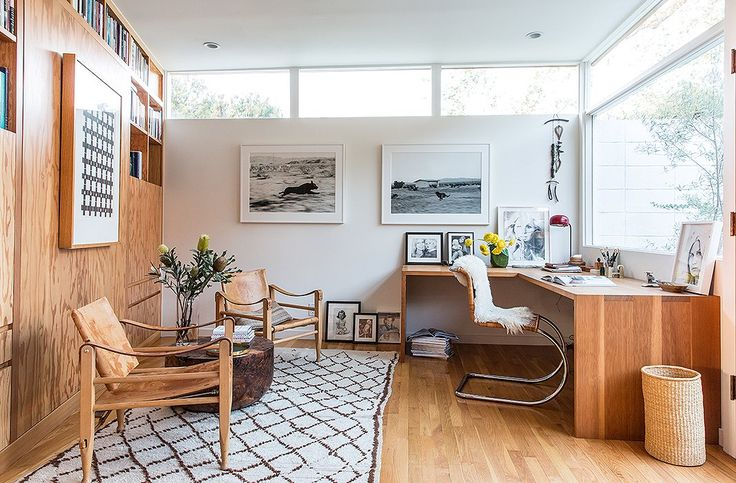 This home office doubles as a guest room courtesy of a hidden Murphy bed and side tables hidden in the built-in bookshelves.
