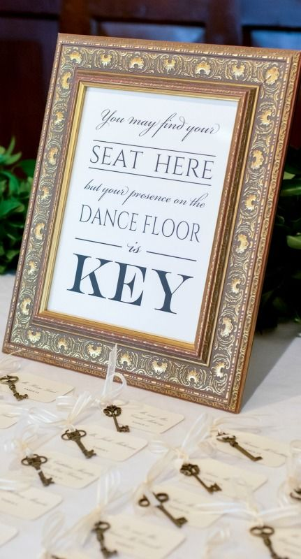 """creative escort card idea: antique brass skeleton keys tied with ivory ribbon and cards with guests names and table numbers + gold picture frame sign with message """"you may find your seat here, but your presence on the dance floor is key!"""""""