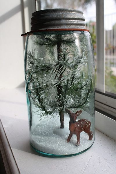 "It's so easy to create your own Christmas terrarium. Just take a Mason jar, fill it with ""snow"" and add a Christmas tree and a reindeer for a DIY Christmas scene that will last forever. Change up the reindeer to a Santa for a different look."