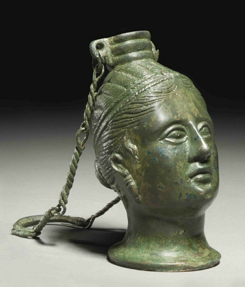 AN ETRUSCAN BRONZE BALSAMARIUM   CIRCA 3RD CENTURY B.C.   In the form of a female head, perhaps Turan (Aphrodite) or a Lasa, hair bound with fillet in melon-coiffure, with tresses escaping, wearing earrings with inverted pyramidal pendants, with articulated eyes, surmounted by ribbed vessel mouth with two suspension loops, with attached suspension chain