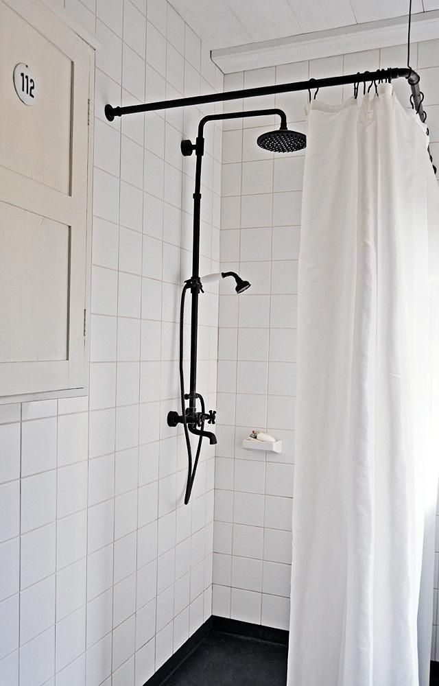 Classic shower in Finland. Black shower curtain rod from old metal fittings; the ceiling is lined with wood sourced from the surrounding forest, protected with a coat of white linseed-oil paint. The ceramic tiles are from Finnish company Pukkila.