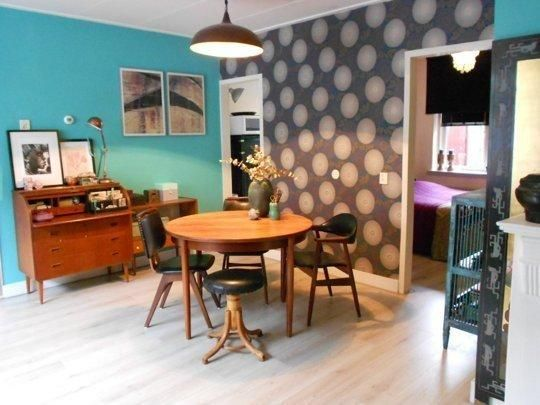 Love the turquoise wall, wood furniture. Not so hot about the wallpaper