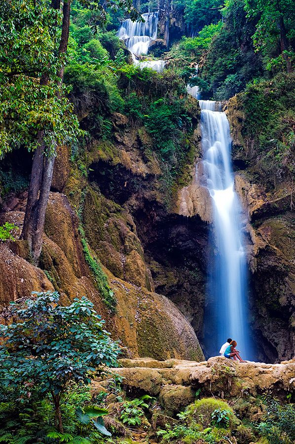 A couple sits in front of the largest cascade at the Kuang Si Falls near Luang Prabang.