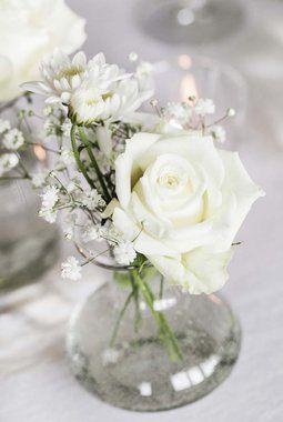 En rose og brudeslør i små glassvaser.