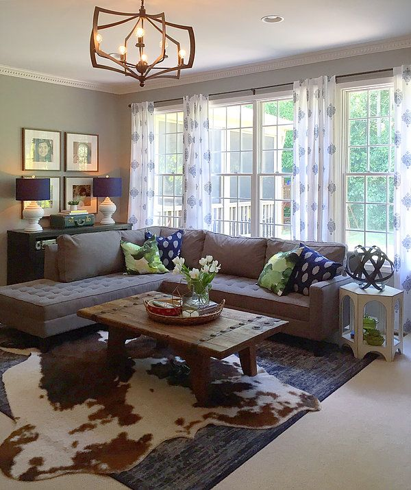 sectional couch in front of windows with side table