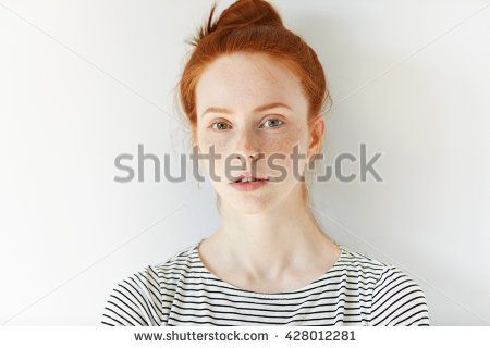 Close up of female teenager with healthy clean fresh skin with freckles wearing sailor shirt, looking at the camera. Portrait of student girl with red hair and blue eyes. Youth and skin care concept