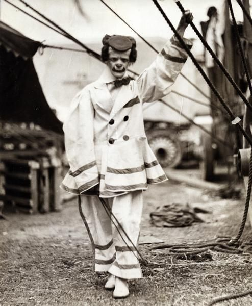 """""""A clown in the Hagenbeck-Wallace Circus stands outside a tent near a wagon, with his left hand holding onto a tent rope. He is wearing a beret-style hat, bow tie, and white shoes."""""""