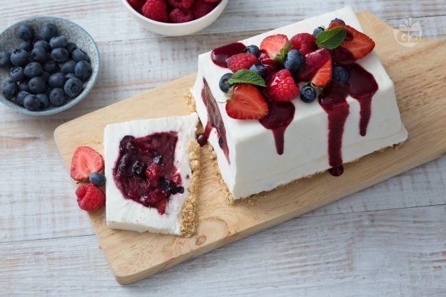 La mattonella allo yogurt con frutti di bosco è un dessert fresco e delicato con panna e yogurt greco, ripieno di frutti, decorato con una coulis.