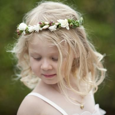This sweet flower girl wears a gorgeous white flower crown