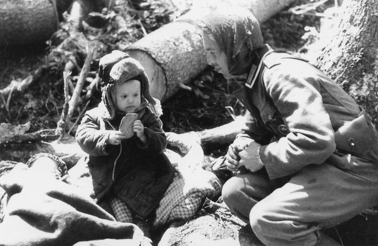 """German soldier giving bread to an orphaned Russian boy. Volkhov area, 1942  Heartbreaking to think this soldier might have had a child the same age at home. It really shows the humility and humanity of the people in the war. Just because they perceived each other as the """"enemy"""" doesn't mean either of them were more or less good than than the other."""