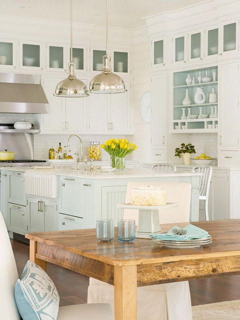 wood table with white cabinets and higher kitchen island. cabinets and interior of shelves painted lightest mint green. different colored cabinets top and bottom.
