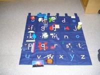 Letterkleed: Dit kleedt bevat alle letters van het alfabet. Het is de bedoeling om voorwerpen die bv. met een 'a' beginnen, zoals armband, op de letter 'a' van het letterkleed te leggen. Op die manier wordt er geluisterd naar de kopjes van een woord en wordt de klank van een woord ook aan een letterteken gekoppeld. Interessante oefening!