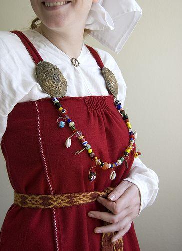 """interesting interpretation of a pleated apron-dress with side-seam trim""  A Kostrup-type dress."