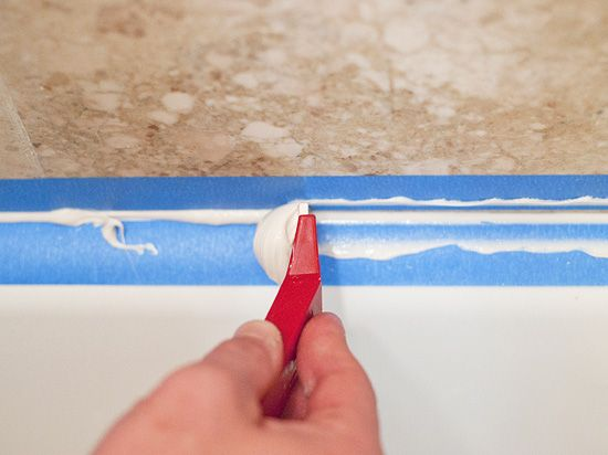 caulk-Once you've worked your way around the entire tub, peel the tape while the caulk is still damp. If you end up with a bit of a harsh line from the tape edge, take another pass or two with your smoothing tool. The overall goal here is to eliminate any lips or edges where water could pool.