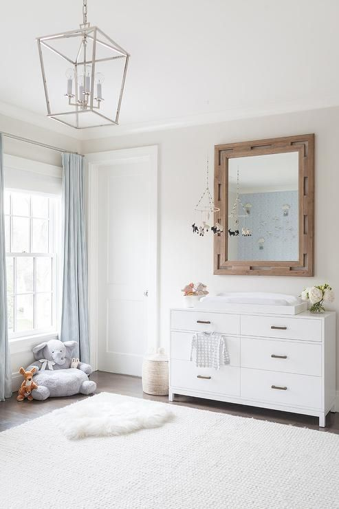 Lovely white and pale blue nursery features a white 6 drawer dresser topped with a white lacquer changing table tray placed beneath a wood framed mirror mounted on a white wall.