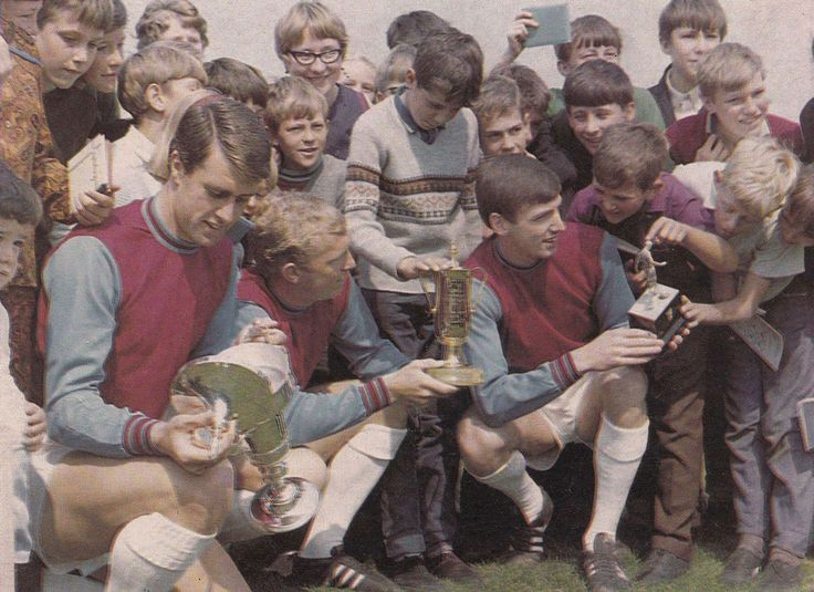 July 1966. West Ham United's World Cup winning trio Geoff Hurst, Bobby Moore and Martin Peters on a meet and greet for local youngsters. And yes that trophy will break if you press too hard.