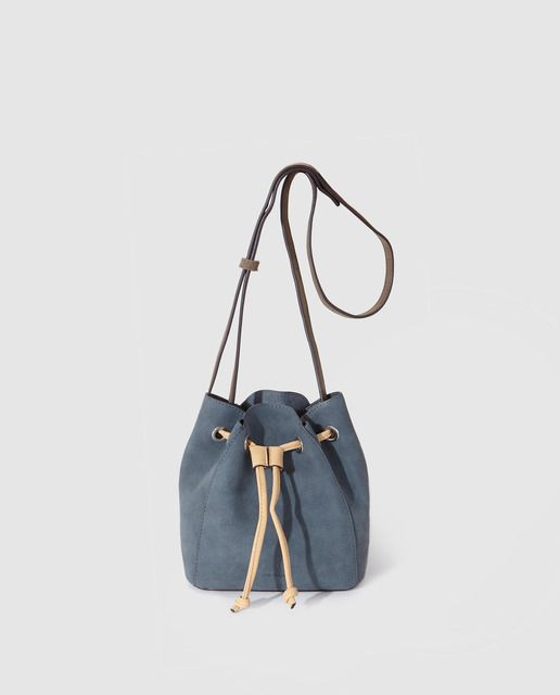Bolso de saco pequeño Even de color azul petróleo con cierre de cuerdas a contraste. Tiene asa larga y lleva grabado el nombre de la firma.