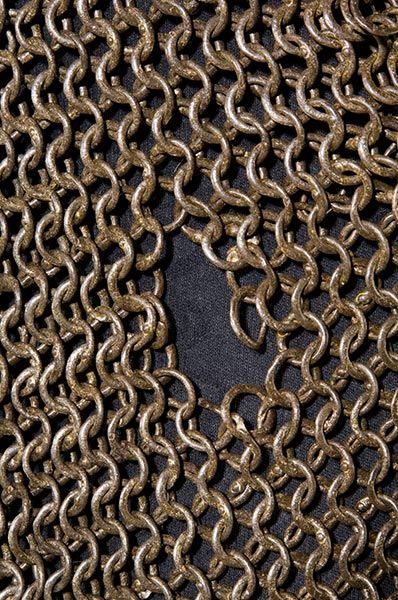 European riveted mail hauberk, detail view, 15th to 16th century, alternating riveted and solid links, thigh-length with elbow length sleeves. The neckline has a front overlapping slit, short collar with two (later?) Iron hook closures, slotted at the bottom front and rear. Length 85 cm. On the right side of the abdomen is an approx. 3 cm hole surrounded by deformed armor rings, possible projectile damage. A12.