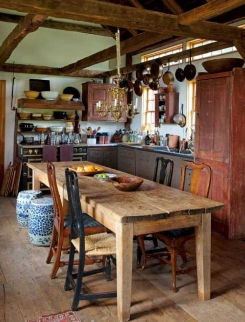 Une longue table en bois avec des chaises différents dans une cuisine rustique