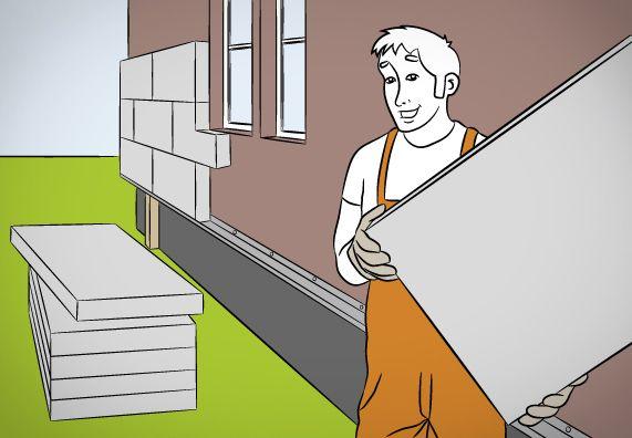 Heimwerker steht mit einer Dämmplatte in der Hand vor der Fassade seines Hauses. Hinter ihm ein Stapel Dämmplatten.