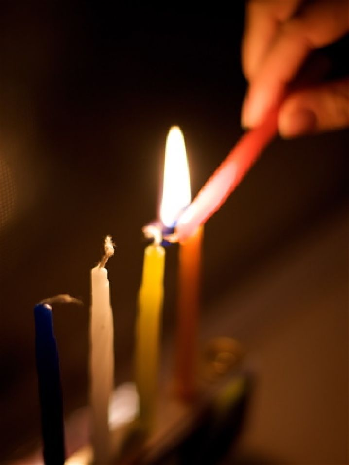 Lighting candles on a Hanukkah menorah. Photo courtesy of Flickr