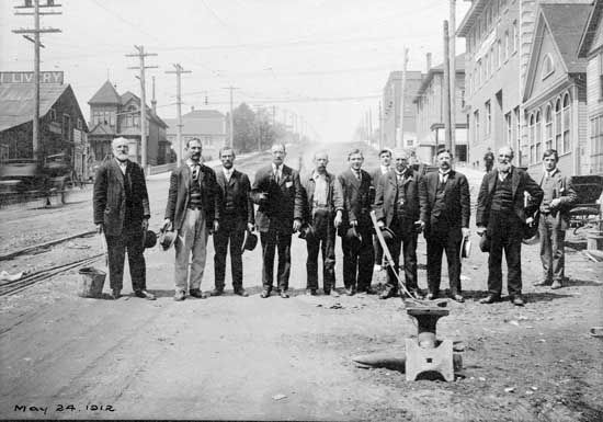 Photograph shows the 1912 Hyack Anvil Salute. A group of men are shown standing on Eighth Street near Columbia Street with the anvil in front of them. The Hyack Anvil Salute was performed in front of Thomas Ovens Blacksmith shop. May 25, 1912.  IHP1111