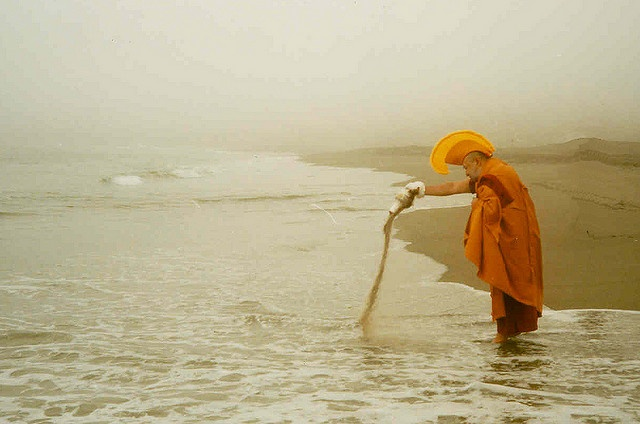 A Tibetan Monk pours the sand from a mandala into the sea.