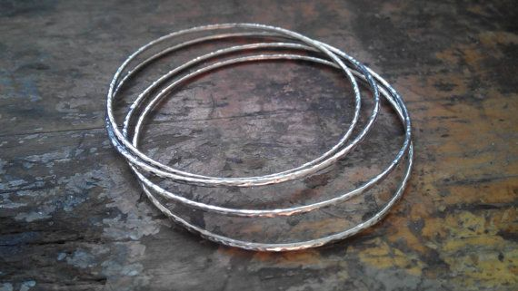 A set of 4 ,7 or 10 silver bangles hammered bangles. Handmade bracelets made from sterling silver.Ideal gift for your friends.Each bangle measures 15mm wide.