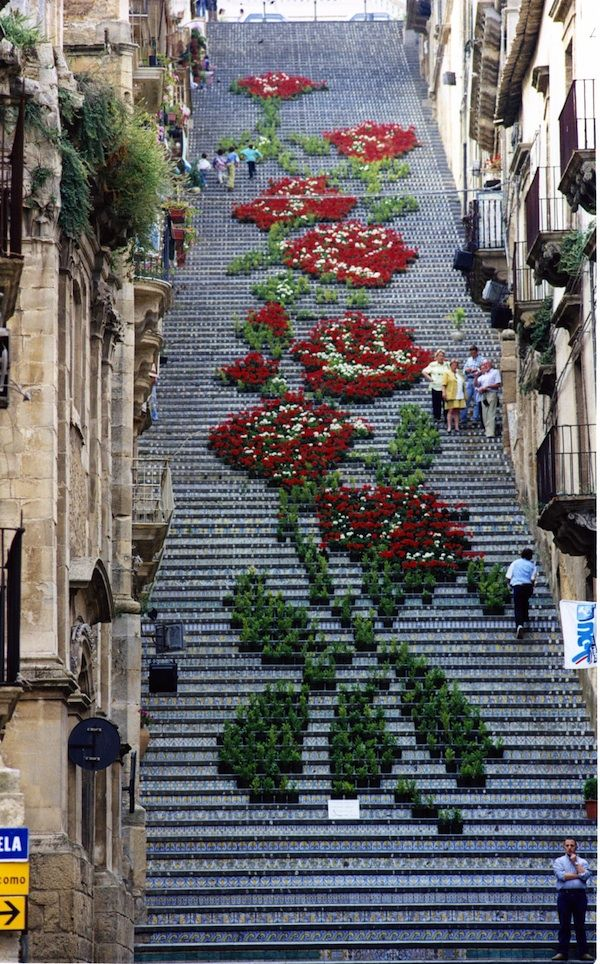 """""""In a small town on the island of Sicily called Caltagirone and you'll witness a landmark that's a sheer beauty. Built in 1608, the Staircase of Santa Maria del Monte has 142-steps which are each decorated with a different ceramic, using styles and figures derived from the millennial tradition of pottery making. During the La Scala Flower Festival, about two thousands potted plants and flowers of different shades and colors are arranged on the historic staircase to create one grand design."""""""