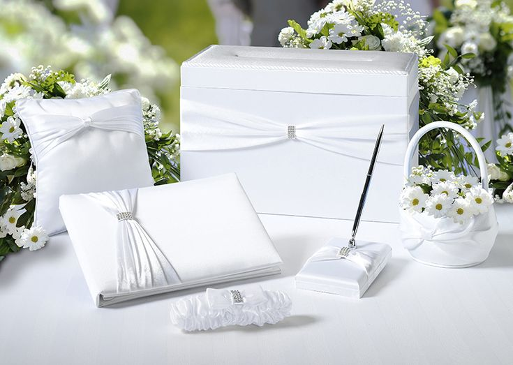 "-This satin wedding set includes six wedding accessories essential to completing your perfect day.  Included are the following items: one 10"" x 6.5"" guest book, one 3.25"" x 5.25"" pen set, one 7.5"" ring pillow, one 7.5"" flower basket and one garter -- all of which are packaged to fit inside the 13.5"" x 7"" x 8.5"" card box.  Most of the accessories (excluding the pillow and basket) are accented by a silver rhinestone ornament.  The silver pen contains black ink."