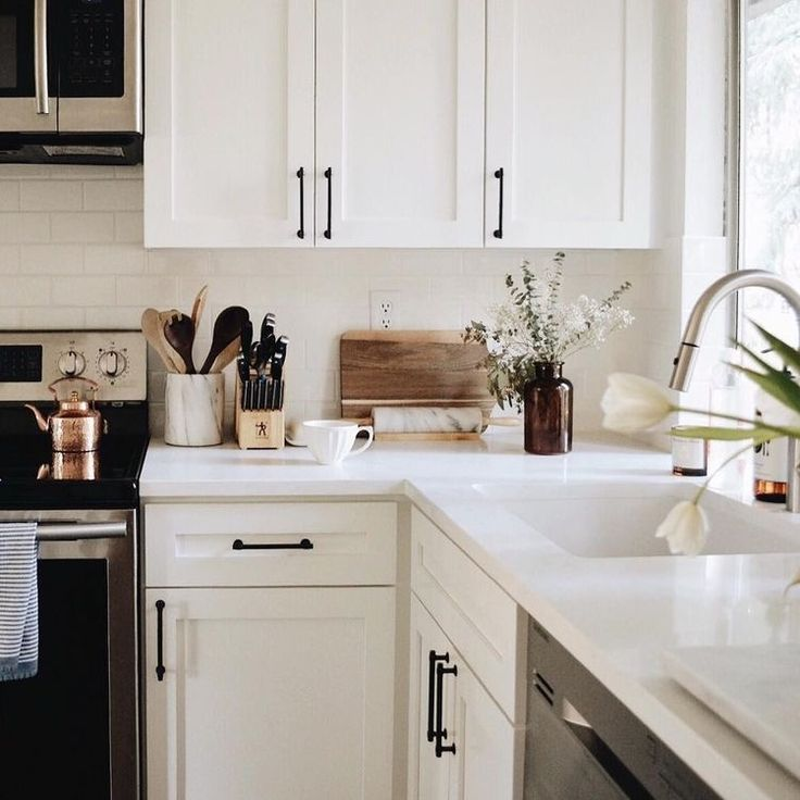 Updated Farmhouse kitchen interior design inspiration with white and black details. Love the pull-down spray faucet and white counters. Small kitchen design layouts