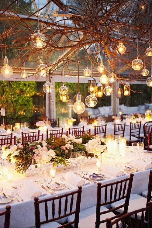 A mixture of exposed bulbs and glass baubles with tea lights, hanging from branches. #weddinglighting