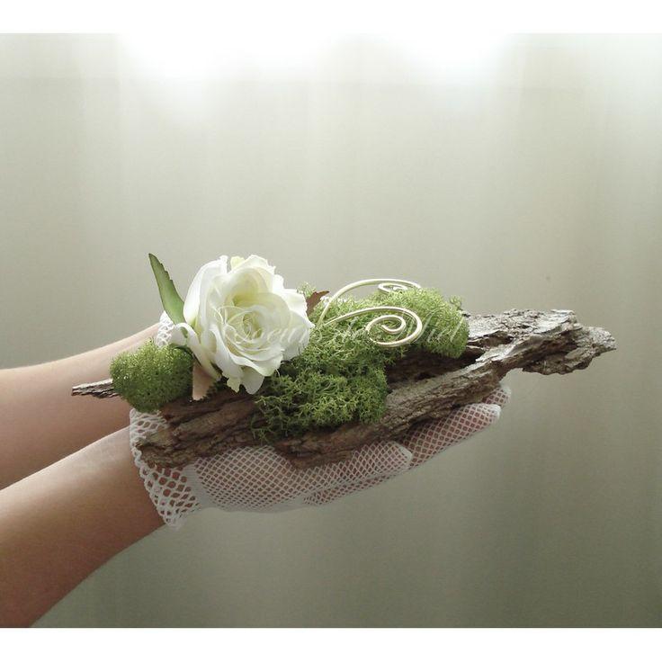 Fin et délicat, ce porte alliance sera idéal pour un mariage au thème nature et elfique. Réalisé à partir d'une écorce, ce coussin d'alliance est orné d'une rose crème et de mousse végétale. Vous pourrez y maintenir vos alliances grâce aux arabesques.