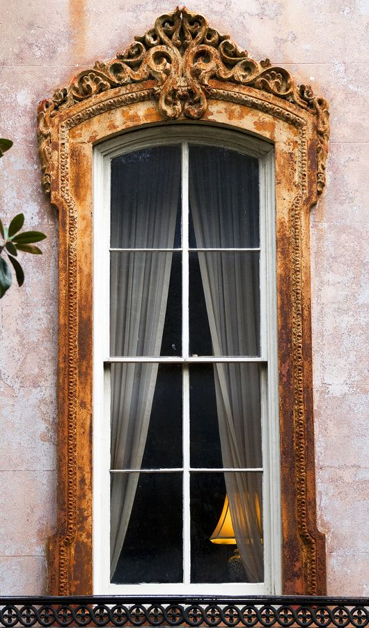 Ornate elegance frames this window, yet reveals a simple curtain and ordinary lamp on the other side.