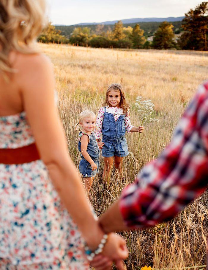 Die Kinder in der Rückseite im Fokus mit den Eltern, die Hände in der Front nicht im Fokus halten