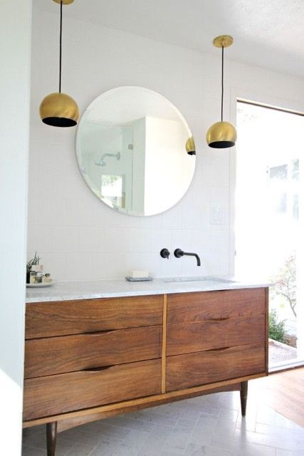 NJ - Re vanity, we could go in one of two directions, either a mid-century furniture piece, something like the one here Or a modern, floating vanity.  Either way, we'd like under-mounted sinks with a marble top or Ceaserstone marble look finish, double sinks or a long trough-style sink. For the finishes on fixtures, we are open to your suggestions.
