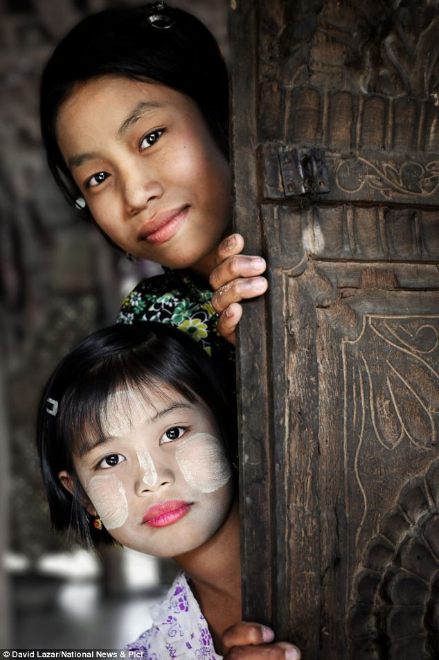 Two young Burmese girls peer around a doorway: One of them has white paint on her face and wears pink lipstick