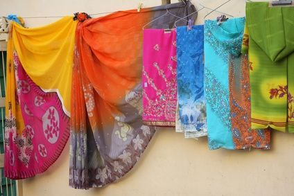 A sari-wrap skirt is a double layer skirt made of two half circles of Asian style fabric. Look for lightweight silk or cotton sari fabrics or any fabric with an Asian look and a soft drape. Saris or sarongs are large enough, generally drape well and come in beautiful colors and patterns. You don't need a pattern as you will construct your own out of butcher paper, wrapping paper or newspaper. Once finished,  wrap it a dozen different ways, wearing it as a skirt, dress or tunic over pants.