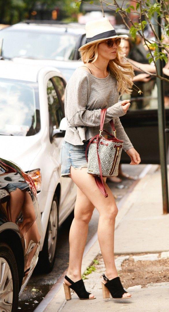 Jennifer Lawrence wears a gray sweater, cutoff shorts, black slingback heels, a fedora, and printed bucket bag