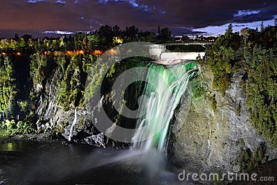Montmorency waterfalls in Quebec - colorful waterfalls illuminated by colored lights at night. View from bottom viewing platform.
