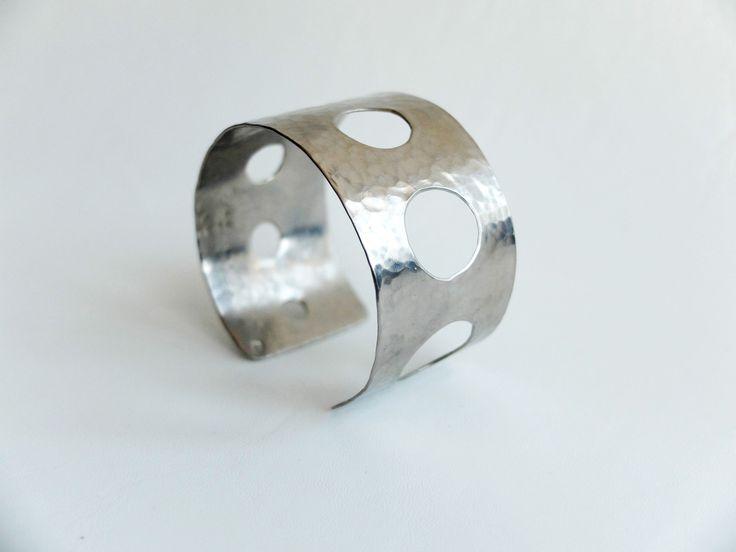 náramek tepaný děrovaný Originální, nápadný náramek je tepaný a vyrobený z nerez oceli. Je lehoučký, elegantní a příjemný na nošení. Má průměr 6 cm. Náramek je ozvláštněn sadou vyvrtaných postupně se zmenšujících otvorů kruhového tvaru. Náramek je výrazný, rozhodně zaujme! Po domluvě je samozřejmě možné udělat jakýkoli jiný průměr náramku.